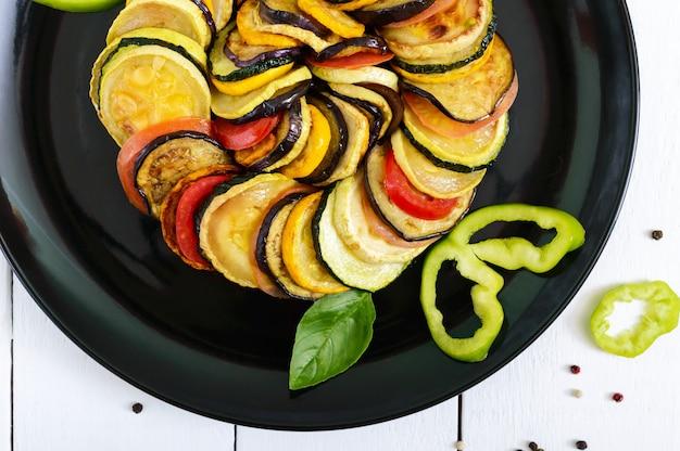 Fried zucchini slices, eggplant, tomato on black plate on white
