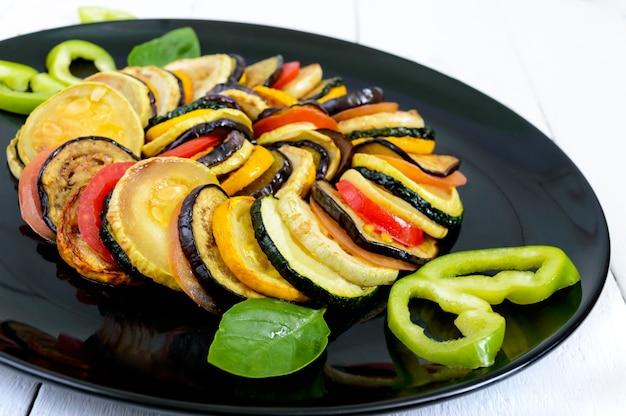 Жареные кусочки кабачков, баклажаны, помидоры на черной тарелке на белом