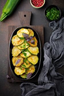 Жареные кабачки с красным острым перцем, базиликом и петрушкой на чугунной сковороде на старой темной поверхности