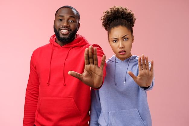 친구가 건강 걱정을 그만 하라고 요구하는 것은 충분히 위험한 제스처가 금지된 손바닥을 들어 올리는 것입니다. 두 아프리카계 미국인 남자 여자는 금연, 분홍색 배경을 설득하는 손 금지 금기 제스처를 보여줍니다