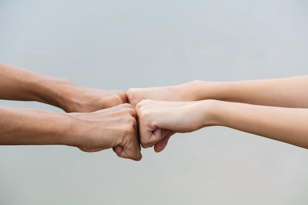 友人の拳は屋外で一緒にぶつかります。同僚間の拳バンプ。友情とチームワークの概念。