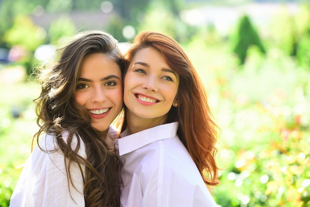 Friend girls forever two cute lovely girl friends posing with smile on green spring background