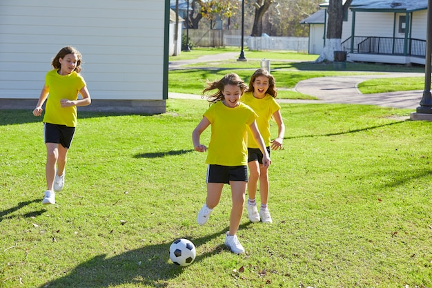 Friend girls teens playing football soccer in a park