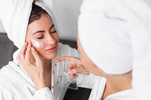Friend helping woman apply under eye patch