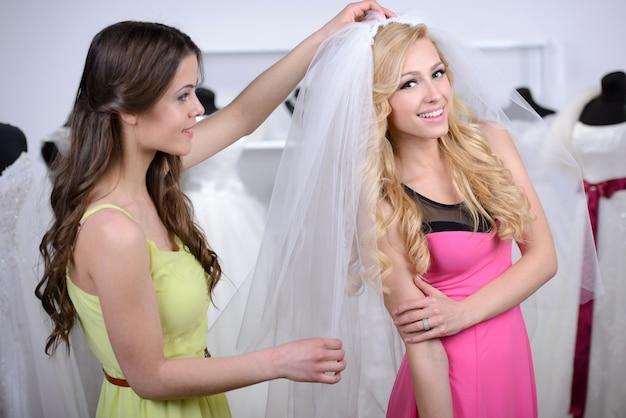 A friend helps a friend choose a veil.
