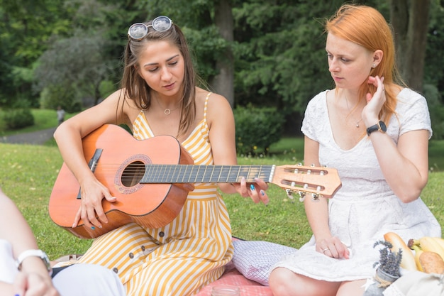 Friend looking at woman playing guitar