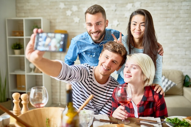 Friend posing for selfie at dinner party