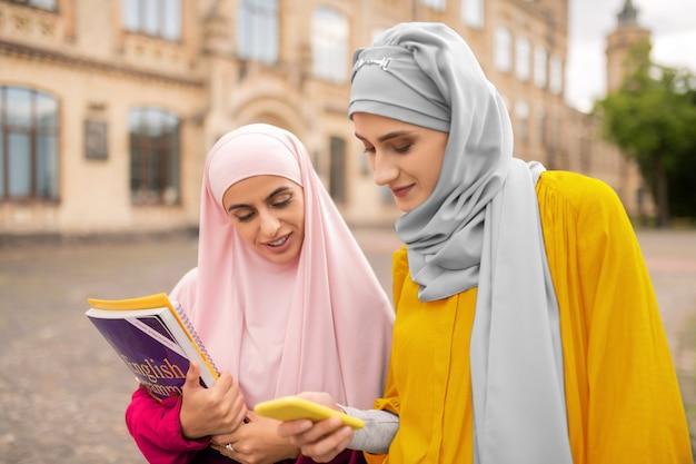 사진을 보여주는 친구. 무슬림 학생에게 노란색 스마트 폰에 사진을 보여주는 가장 친한 친구