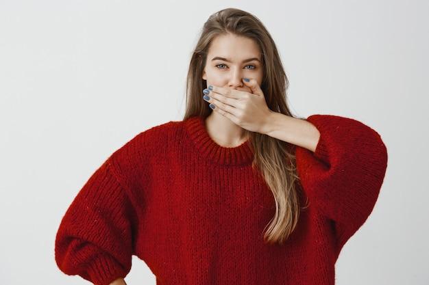Друг клянется не говоря ни слова о секрете. портрет симпатичной женственной женщины в модном свободном свитере, прикрывающем рот ладонью, дающим обещание хранить молчание