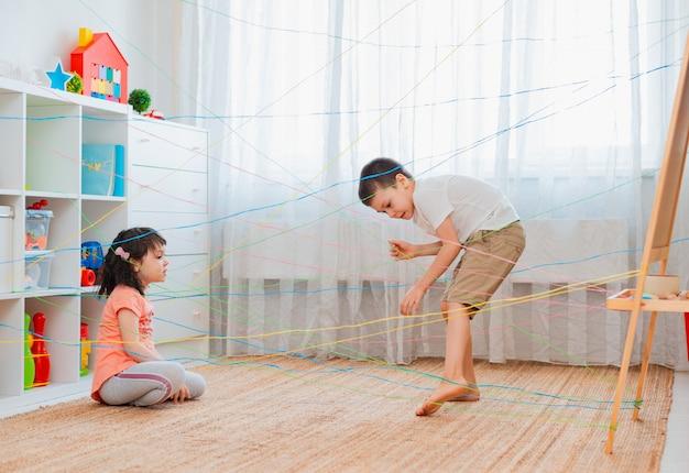 小さな女の子の男の子の兄弟、兄弟、friendchildがロープの網、屋内のゲームの障害物クエストを登っていきます。