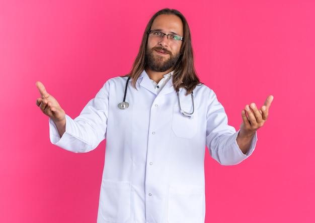 歓迎のジェスチャーをしている眼鏡と医療ローブと聴診器を身に着けているフレンドリーな成人男性医師