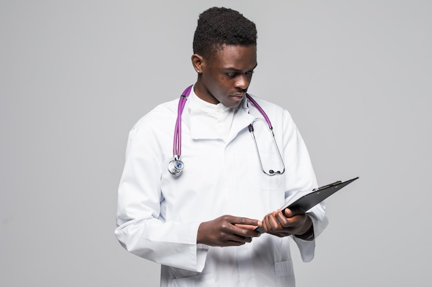 Friendly afro-american doctor holding a clipboard and smiling at the camera isolated on gray background