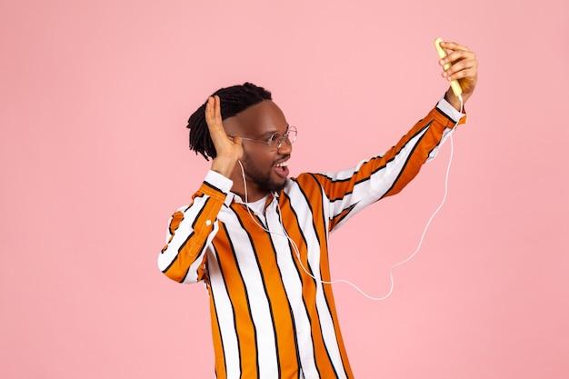 스트리밍, 이어폰을 통해 추종자들과 이야기, 전화 카메라에 포즈를 취하는 친절한 아프리카계 미국인 남자