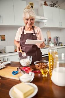Дружелюбная стареющая женщина готовится к выпечке