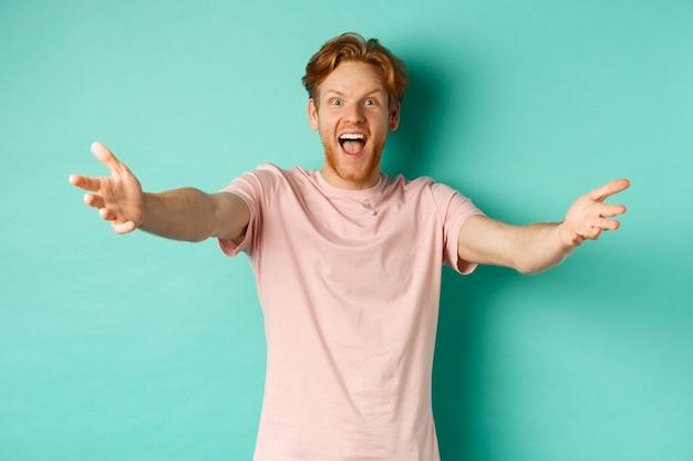 진저 머리를 한 친절하고 행복한 청년은 따뜻한 환영으로 손을 뻗고, 포옹을 하고 즐겁게 웃고, 민트 배경 위에 티셔츠를 입고 서 있습니다.