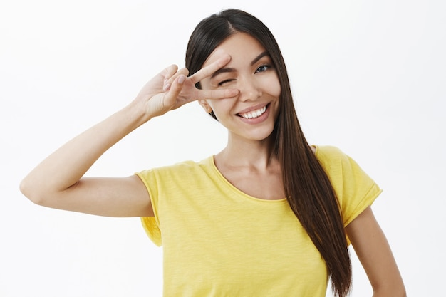 平和を示して幸せに笑っている長く暗い健康な髪を持つフレンドリーで平和な格好良い感情的なアジアの女性