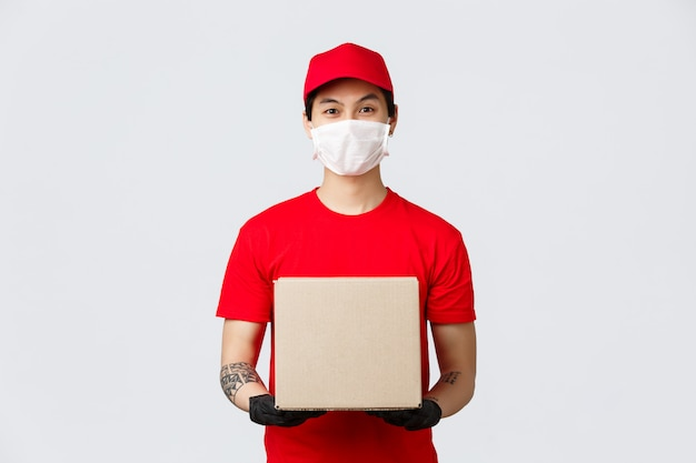 Friendly asian delivery guy with box parcel waiting for client open door. courier in medical mask and protective gloves bring package to client during covid-19 pandemic