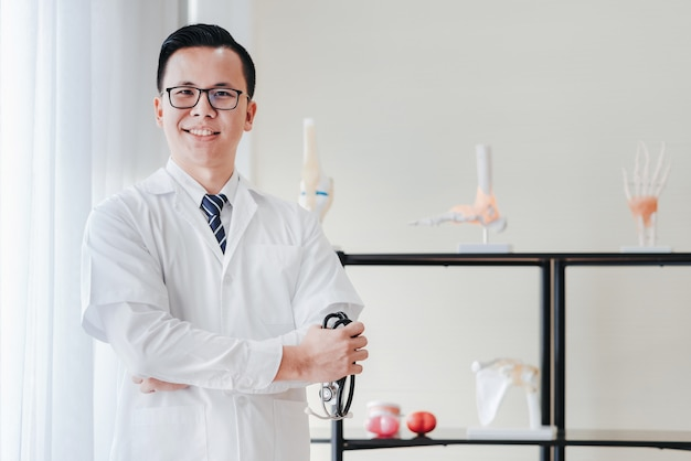 Friendly asian doctor olding stethoscope in hand in his office