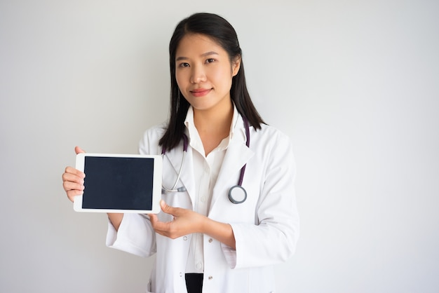Friendly asian female doctor showing tablet screen