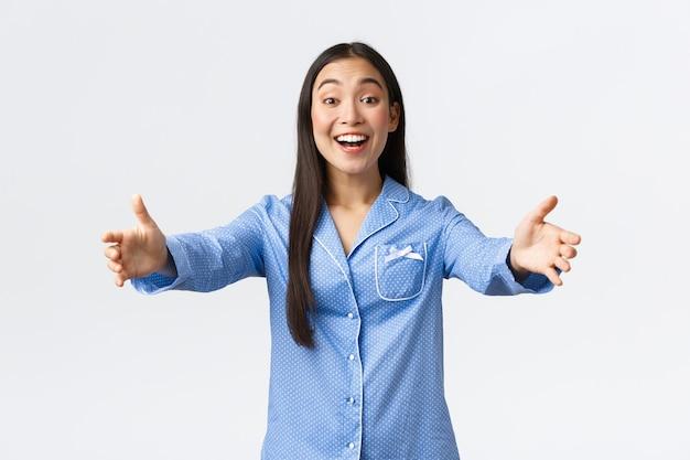 青いパジャマを着たフレンドリーなアジアの女の子は、彼女の外泊パーティーにガールフレンドを歓迎し、幸せそうに笑って、白い背景の上にパジャマで立って、挨拶または抱擁するために手を伸ばします