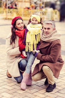 Friendly atmosphere. beautiful girl looking straight at camera while caressing her parents