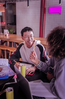 Friendly atmosphere. joyful asian schoolboy keeping smile on his face while being in all ears