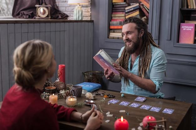 친절한 분위기. 그녀에게 읽을 책을 추천하면서 그의 방문자에게 웃고 긍정적 인 행복한 사람