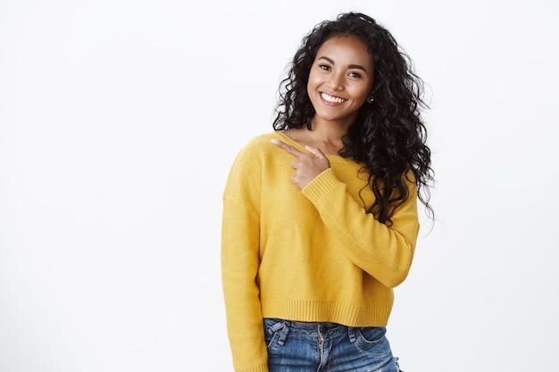 黄色のスタイリッシュなセーターのフレンドリーで魅力的なアフリカ系アメリカ人の女性は満足して笑って、自信を持ってのんきに見え、クールなニュースを共有し、左を指して、アドバイスを与えるチェックアウトクールな店