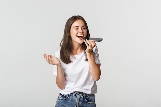 Дружелюбная привлекательная брюнетка девушка разговаривает по динамику, записывает голосовое сообщение на смартфон, белый.