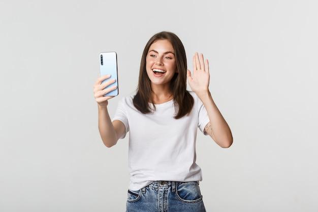 Дружелюбная привлекательная девушка приветствует, машет рукой на смартфон во время видеозвонка, разговаривает.