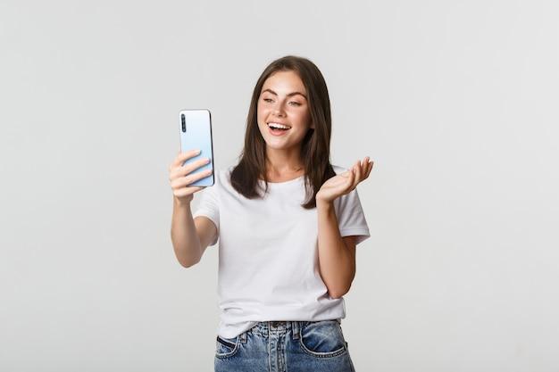 Amichevole ragazza attraente videochiamata amico, sorridente e conversazione, che tiene smartphone, bianco.