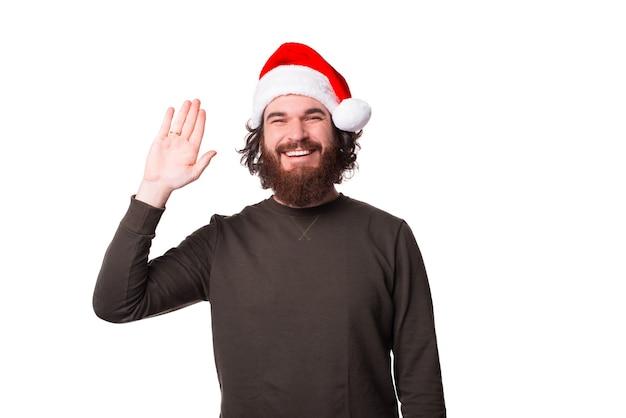 산타 클로스 모자를 쓰고 hello 제스처를 만드는 친절한 수염과 행복한 남자