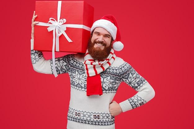 笑顔で大きなギフトボックスを運ぶサンタ帽子のフレンドリーなひげを生やした男