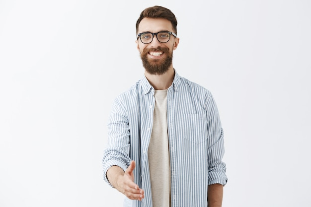 Friendly bearded man posing against the white wall