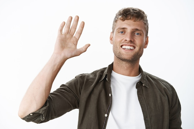 Amichevole ragazzo biondo che saluta salutando salutando in modo amichevole, sorridendo ampiamente, essendo di buon umore, posando freddo e spensierato contro il muro grigio mentre saluta i compagni