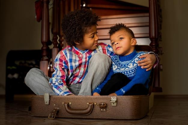 フレンドリーな男の子がスーツケースの中に座っています。 2人の親しみやすいアフロの子供たち。兄弟よ、私を見てください。写真に微笑んでください。