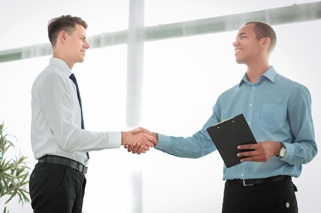ぼやけた背景に握手するフレンドリーなビジネスの人々