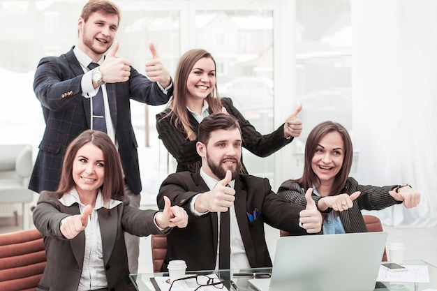 Friendly business team makes a gesture of thumbs up