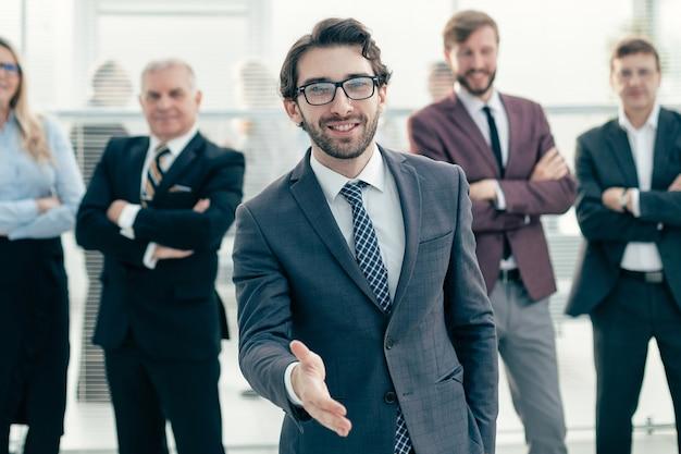 握手のために彼の手を差し伸べるフレンドリーなビジネスマン