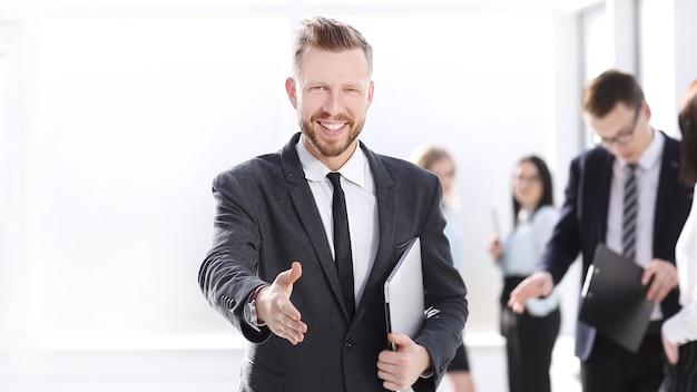 彼のオフィスにあなたを歓迎するフレンドリーなビジネスマン。コピースペースのある写真