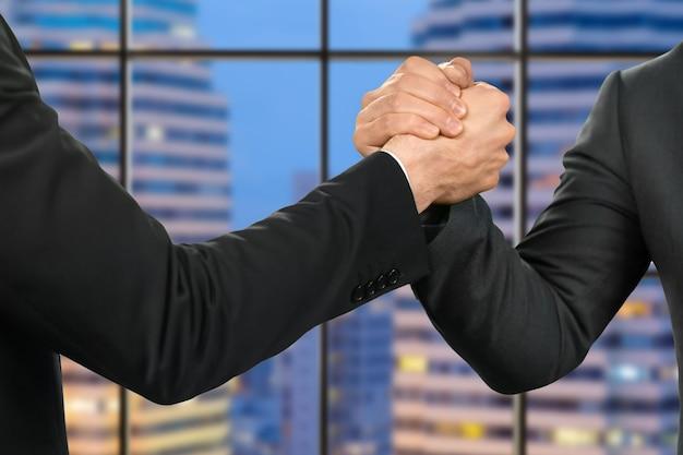 フレンドリーなビジネスマンが握手します。パートナー&#39;メガロポリスの背景に握手。市はその指導者を待っています。自信を持って信頼できる人。