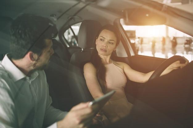 Приветливый продавец автомобилей разговаривает с молодой женщиной и показывает новый автомобиль в автосалоне. подписание контракта.