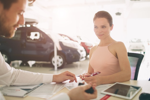 Friendly car salesman talking to a young woman and showing a new car inside showroom signing of contract