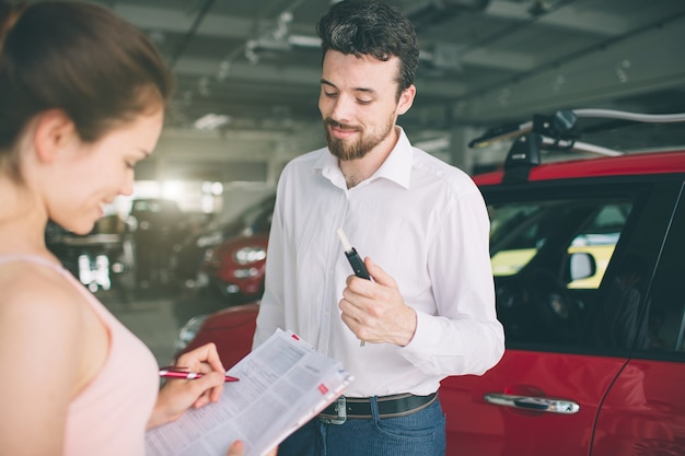 Friendly car salesman talking to a young woman and showing a new car inside showroom signing of contract.