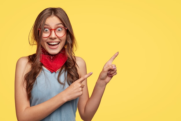 Friendly carefree female shop assistant points right, has board smile, advertises new outfit with big discounts, wears transparent glasses, models against yellow  wall with copy space for slogan