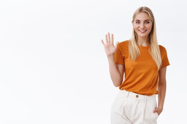 Amichevole, spensierata sfacciata donna bionda attraente in maglietta arancione, pantaloni alzano il palmo e agitando la mano in gesto di saluto, sorridendo con gioia saluta o saluta, benvenuto o ospite, sfondo bianco