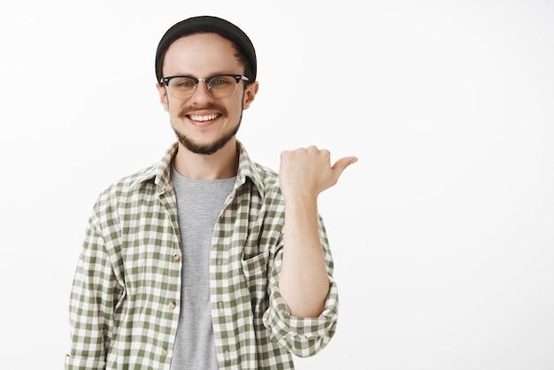 Gentile cliente maschio spensierato e soddisfatto di bell'aspetto con la barba in occhiali berretto nero e camicia verde casual che punta a destra con il pollice e sorride gioiosamente dando consigli o mostrando la via