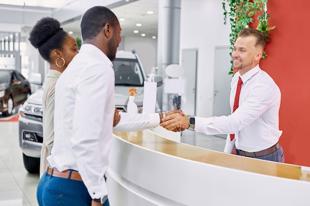 Friendly caucasian man administrator and consultant of dealership welcomes clients