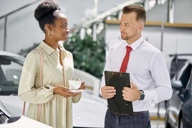 フレンドリーな白人セールスマンが黒人の顧客の女性と話します