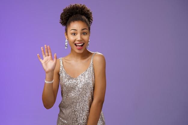 Дружелюбная очаровательная общительная афро-американская женщина видит друга в ночном клубе, широко улыбаясь, здоровается, машет рукой, приветствует, приветствует общительный, радостный встречу, стоит на радостном синем фоне.